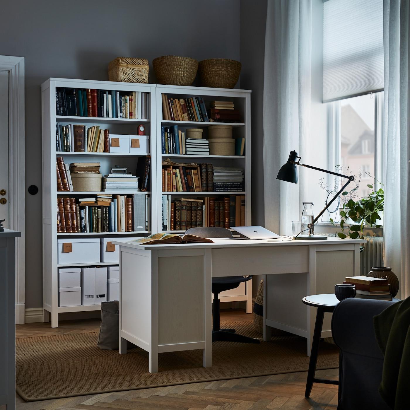 Rum med vitt skrivbord som står centralt i rummet, matchande höga bokhyllor bakom skrivbordsstolen och grön arbetslampa på skrivbordet.