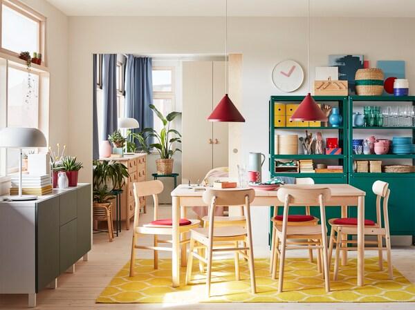 Ruokailutila, jossa on koivusta valmistettu ruokailuryhmä, keltainen matto, harmaanvihreä senkki ja kaksi punaista kattovalaisinta.