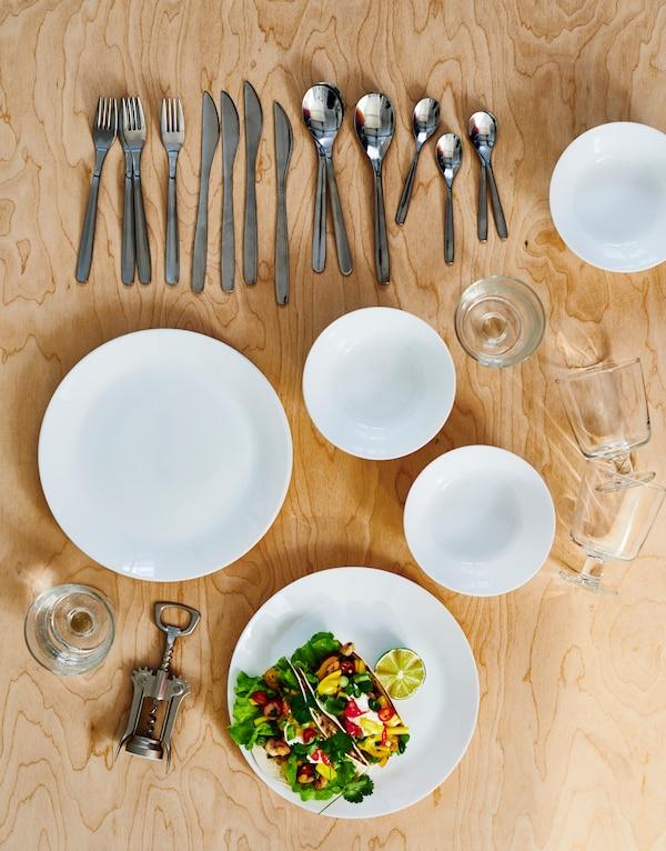 Ruokailuvälineet vaalealla puupinnalla: valkoiset OFTAST-levyt ja -kulhot, MOPSIG-ruokailuvälineet, viinilasit ja viinipullojen avaaja.