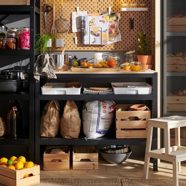 Ruokakomero, jossa on pieni työpiste kokkausta varten, hyllyllä erilaisia laatikoita ja seinällä puinen SKÅDIS-säilytystaulu.