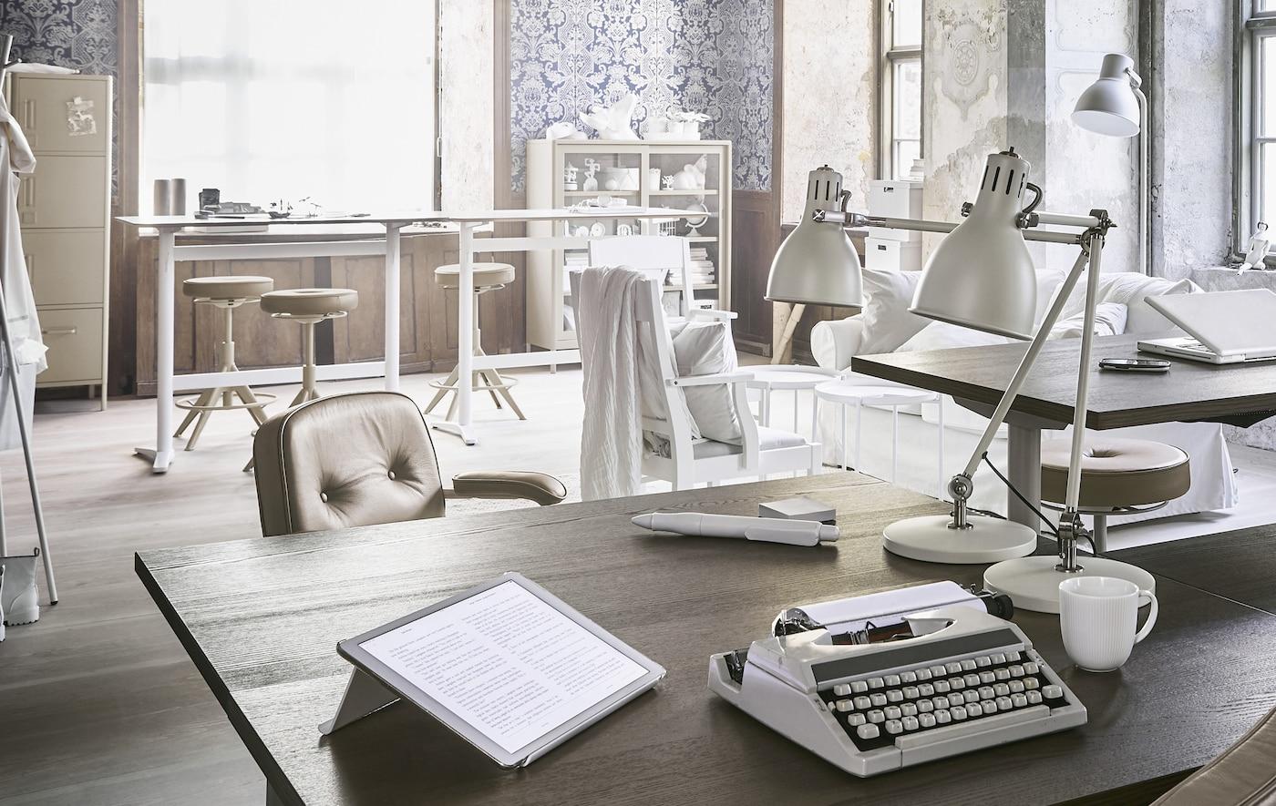 Ruskea työpöytä toimistossa, jossa kirjoituskone, tabletti ja kaksi pöytävalaisinta.