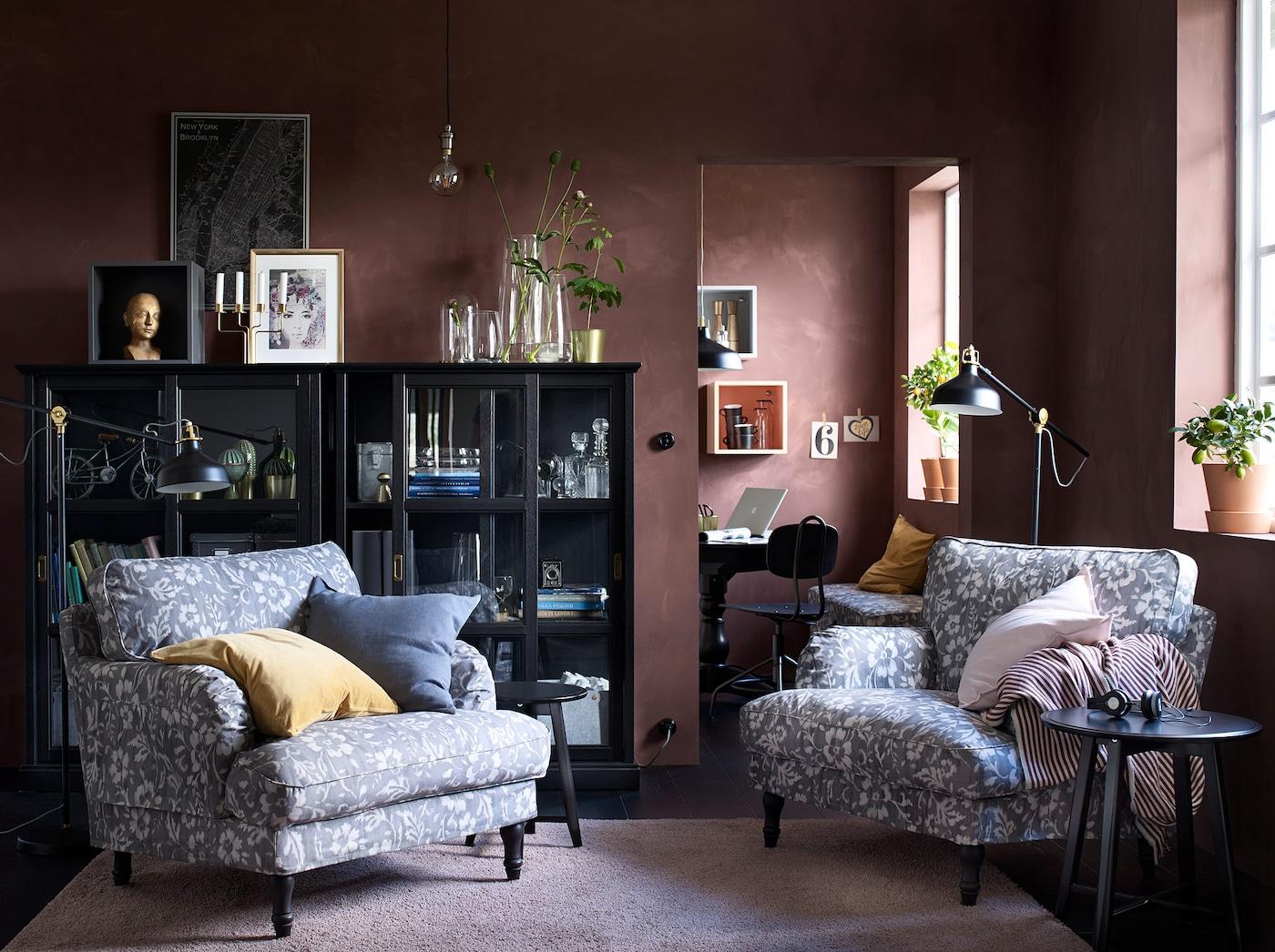 Ruskeanmusta olohuone, jossa kaksi suurta nojatuolia harmaanvalkoisilla kukkakuvioiduilla päällisillä.