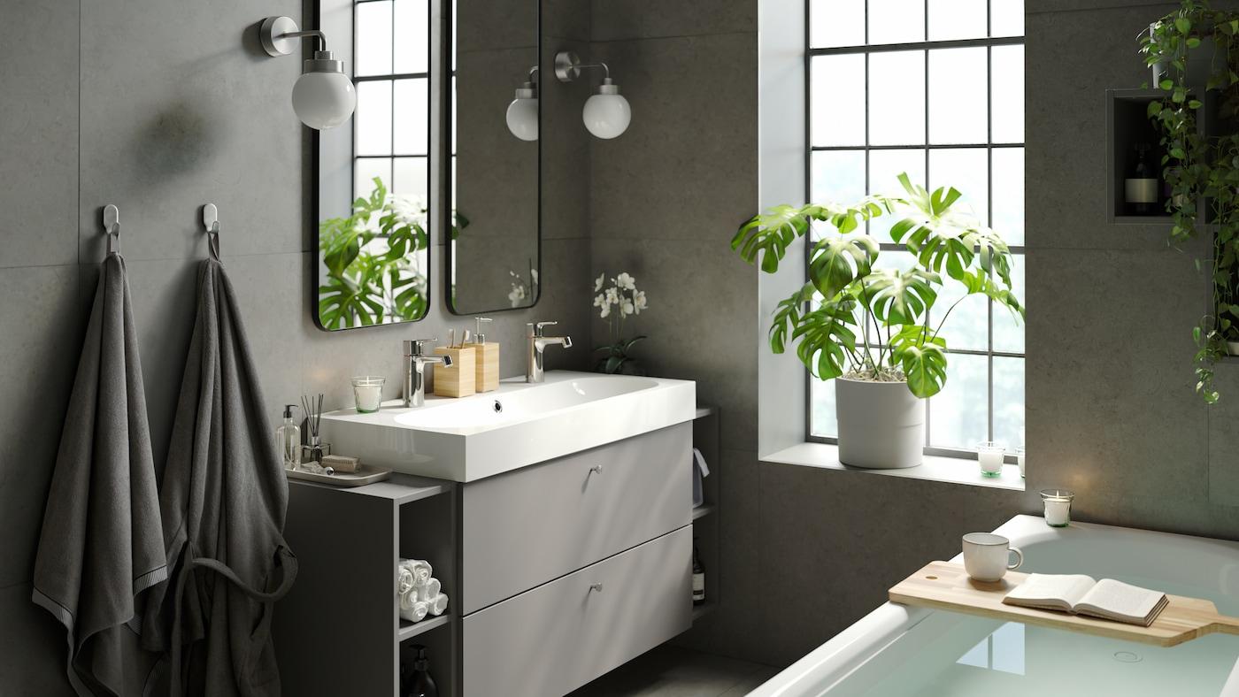 Rustieke en moderne badkamer met elegant ligbad, brede dubbele wastafel met opbergruimte , dubbele spiegels en binnen groene planten.