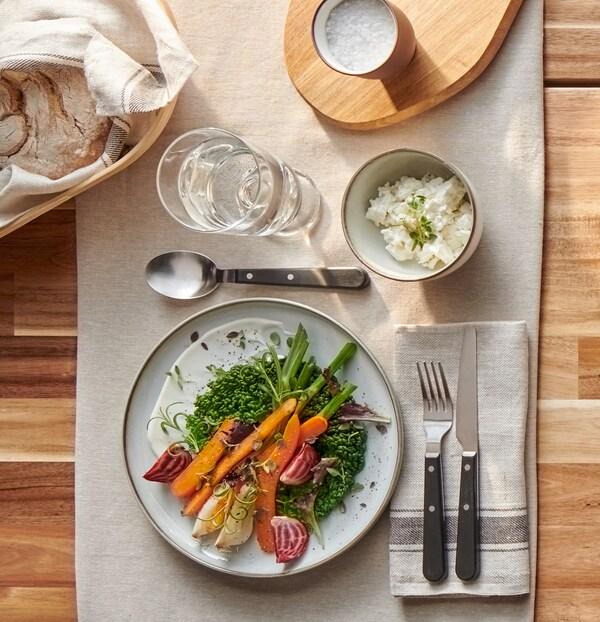 Rustikalan sivo-smeđi tanjur sa šarenim povrćem, izdržljivim LIVNÄRA priborom za jelo i čašom vode na bež stolnjaku.