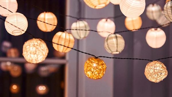 Různé typy osvětlovacích řetězů SOLVINDEN s LED diodami visí v noci na balkóně za oknem a svítí.