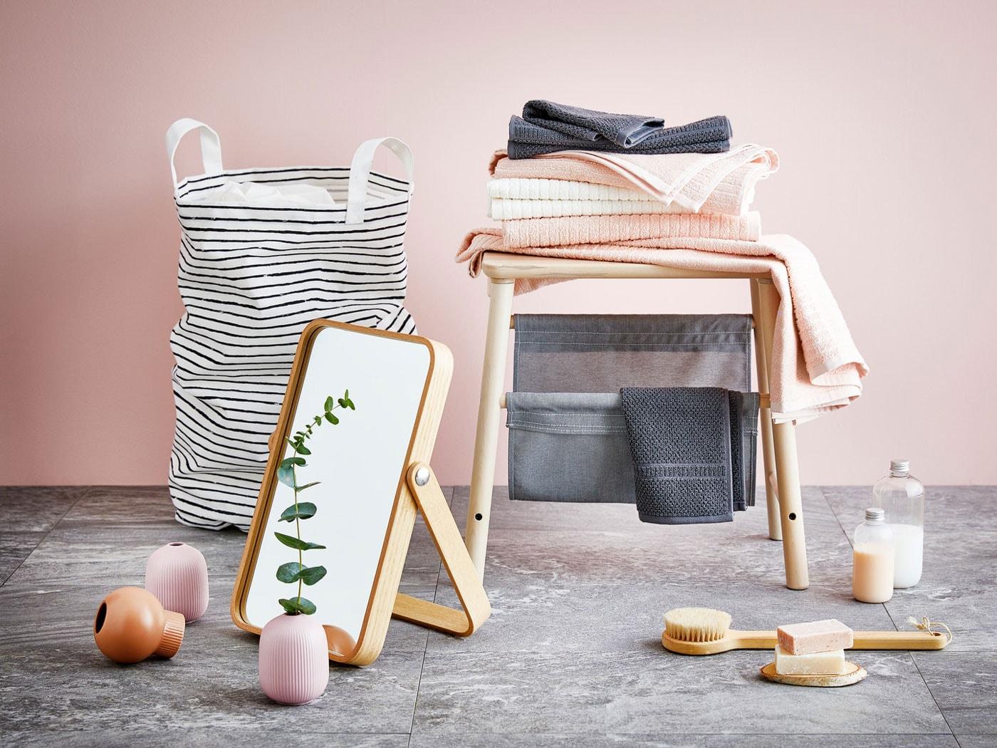 Růžová koupelna s dřevěným zrcadlem, kartáčem, lahvičkami se sprchovým gelem a růžovými, bílými a šedými ručníky ležícími na stoličce.