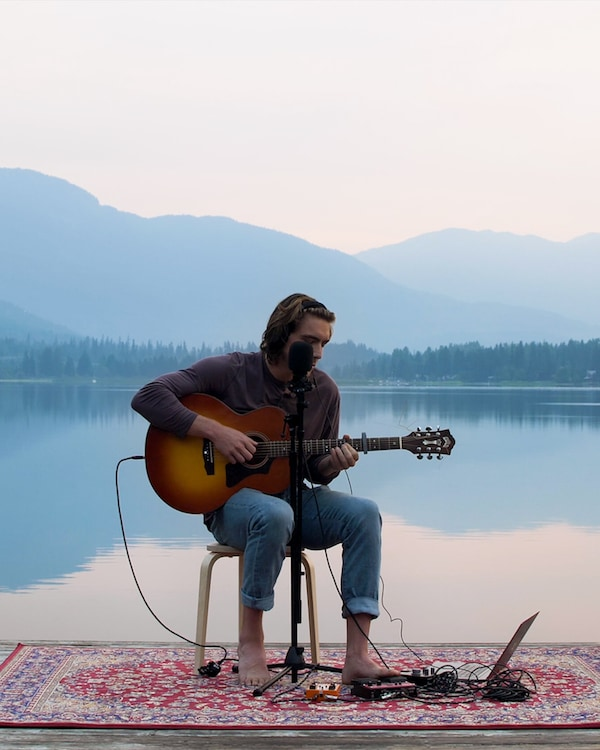 Ryan Harris holds a guitar, sitting on a stool placed on a red patterned rug, on a lakeside dock with the Rocky mountains in the background.