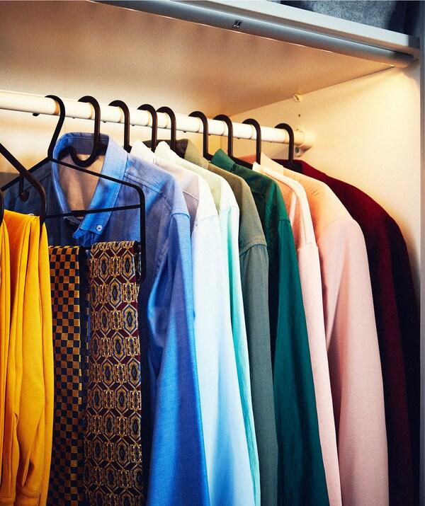 Rząd koszulek i akcesoriów na wieszakach na drążku w szafie, część szafy oświetlona i wyposażona w listwę oświetleniową LED.