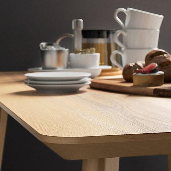 Saarniviiluisella LISABO-pöydällä kahvikuppeja, leikkuulaudalla hunajapurkki ja sämpylöitä.