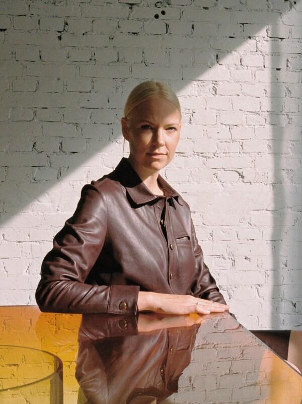 นักออกแบบ Sabine Marcelis นั่งอยู่กับโต๊ะที่ด้านบนมีพื้นผิวมองเห็นเงาสะท้อน