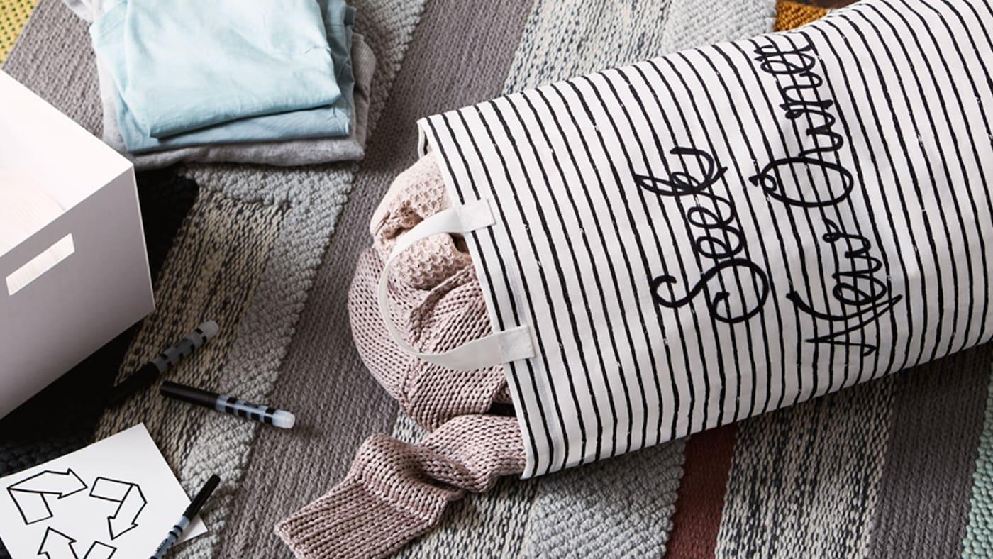 """Sacco per il bucato in tessuto con la scritta """"seek new owner"""", con vestiti al suo interno, su un tappeto accanto a una scatola, penne e un'etichetta con il simbolo del riciclaggio - IKEA"""