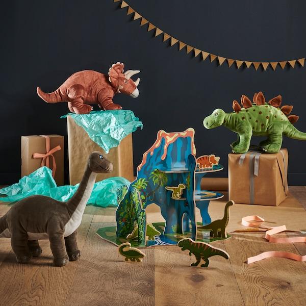 Sada plyšových dinosaurů rozmístěných po místnosti.