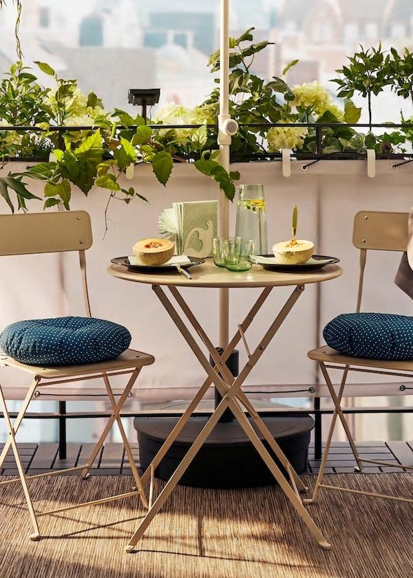 Sada vonkajšieho nábytku s rastlinami v pozadí - stôl a stoličky so sedákmi, dotvárajúce príjemnú atmosféru.