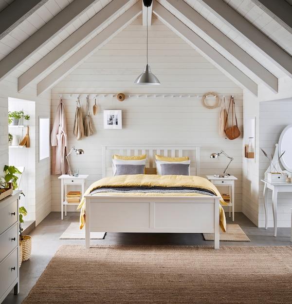 Säng med gula sängkläder står i ett stort och ljust rum med högt i takt