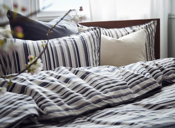 Sängyllä on RANDGRÄS-puuvillavuodevaatteet, tyynyjä ja peitto valkoisen ja harmaan sävyissä.