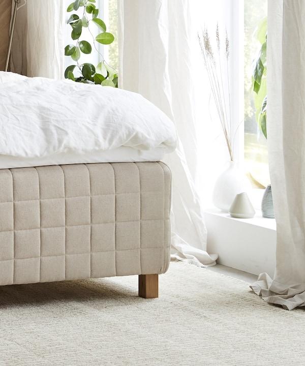 Sängystä näkyy kulma, sängyllä on valkoiset lakanat. Isot ikkunat joissa on valkoiset ohuet verhot. Patjanvalintaopas - IKEA