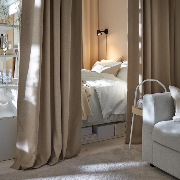 Sänky, joka on hiukan piilotettu sitä ympäröivien beigenväristen verhojen taakse, luo mukavan makuutilan.