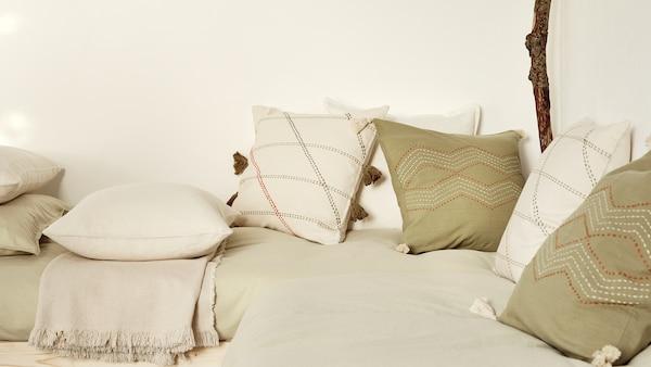 Sänky, jonka päällä on paljon erilaisia koristetyynyjä.