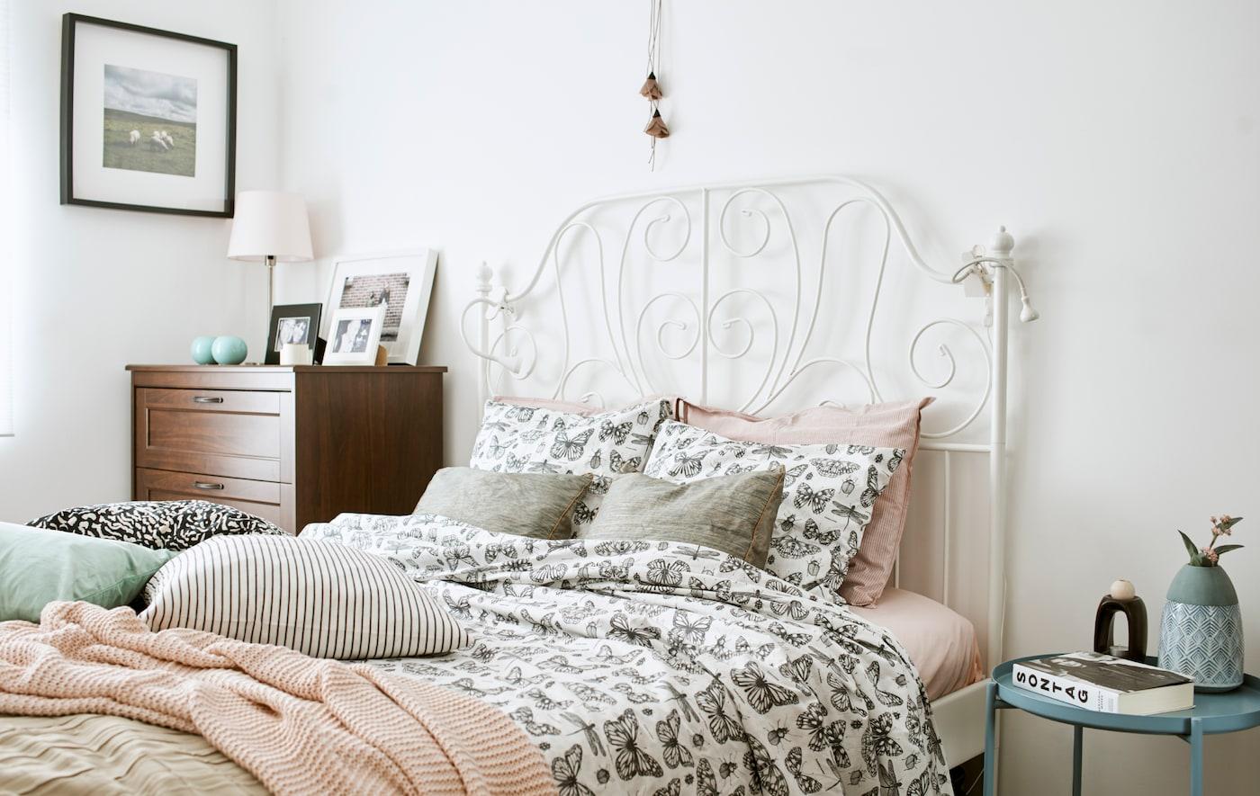 Sänky, jossa on valkoinen takorautainen sängynpääty, pussilakanatT, joissa on mustavalkoiset perhoskuviot, vaaleanpunainen neulehuopa ja tyynyt.