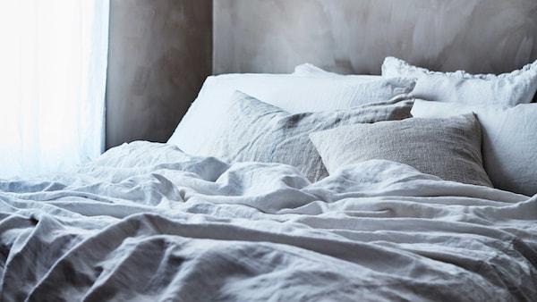 Sänky, jossa vaaleat vuodevaatteet ja tyynyjä