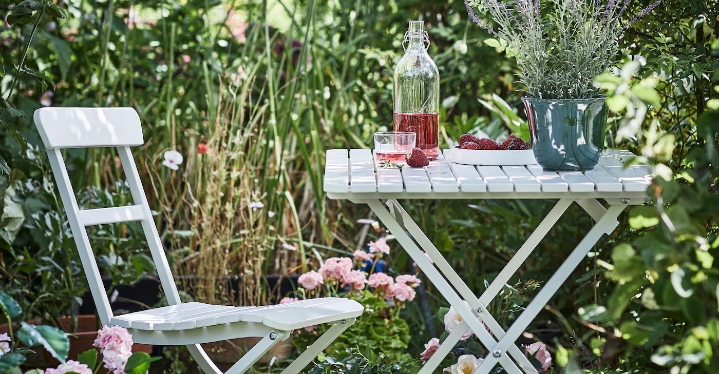 Saftevand på et havebord ved en havestol i en have med masser af blomster og vildt