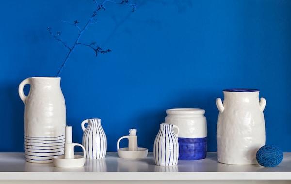 サイドテーブルに置いた素朴な手づくり風の2色使いの陶器の花瓶、水挿し、キャンドルホルダー。