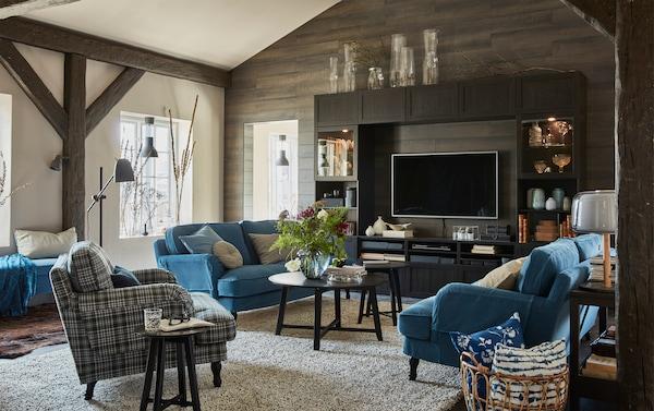 Sala com sofás STOCKSUND à volta de uma mesa baixa com uma jarra com flores em cima e combinação de móvel para TV BESTÅ com uma TV.