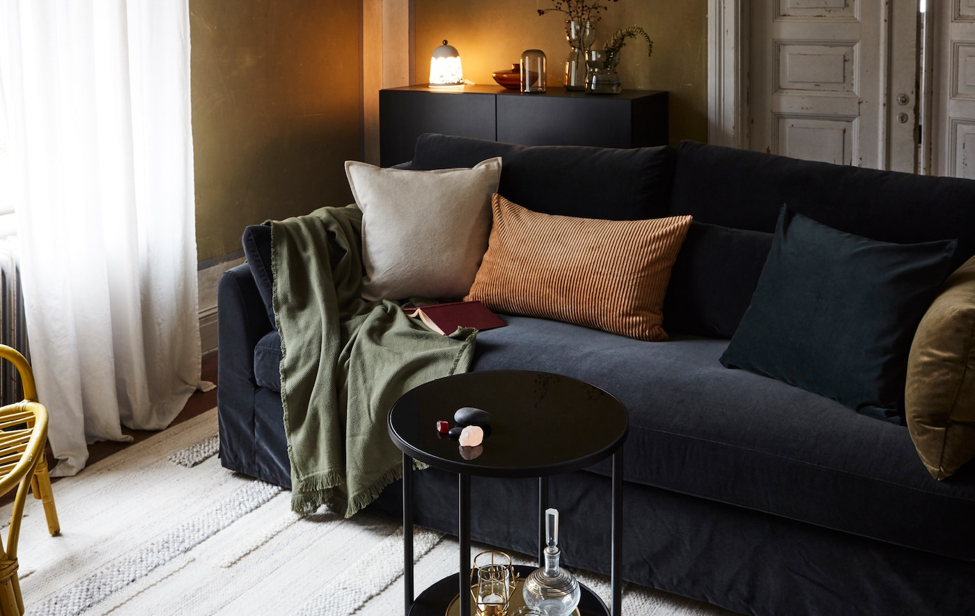 Sala com um sofá, almofadas, manta, tapete, mesa pequena, um aparador com um candeeiro, jarras e uma poltrona em rota.