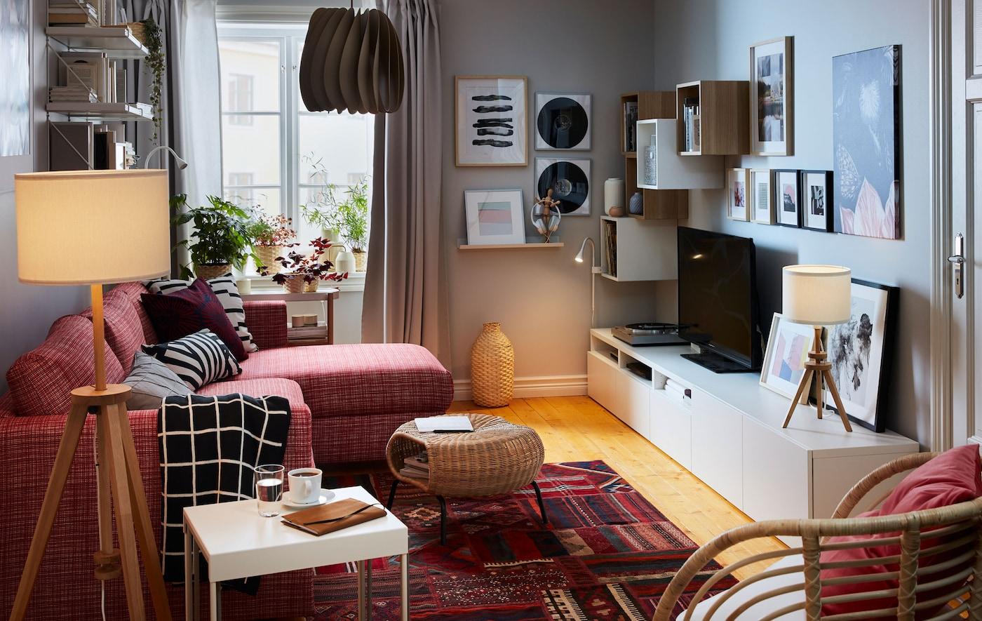 Sala compacta com um sofá-cama com chaise longue num lado e aparador, arrumação, TV, sistema de som e arte no outro.
