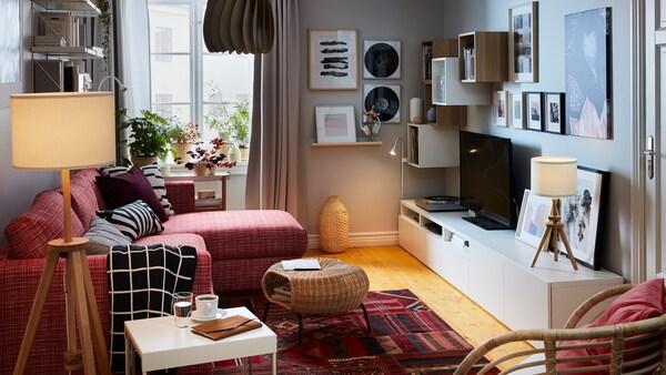 Sala compacto con sofá cama e chaiselongue nun lateral; aparador, almacenaxe, televisión, equipo de música e láminas na outra.
