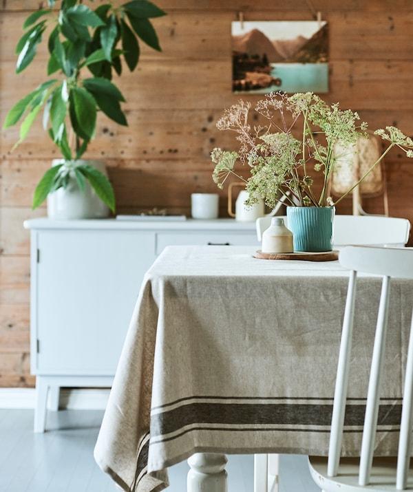 Sala da pranzo rustica con tavolo in legno, tovaglia e centrotavola con portavasi turchese scanalato contenente dei fiori selvatici- IKEA