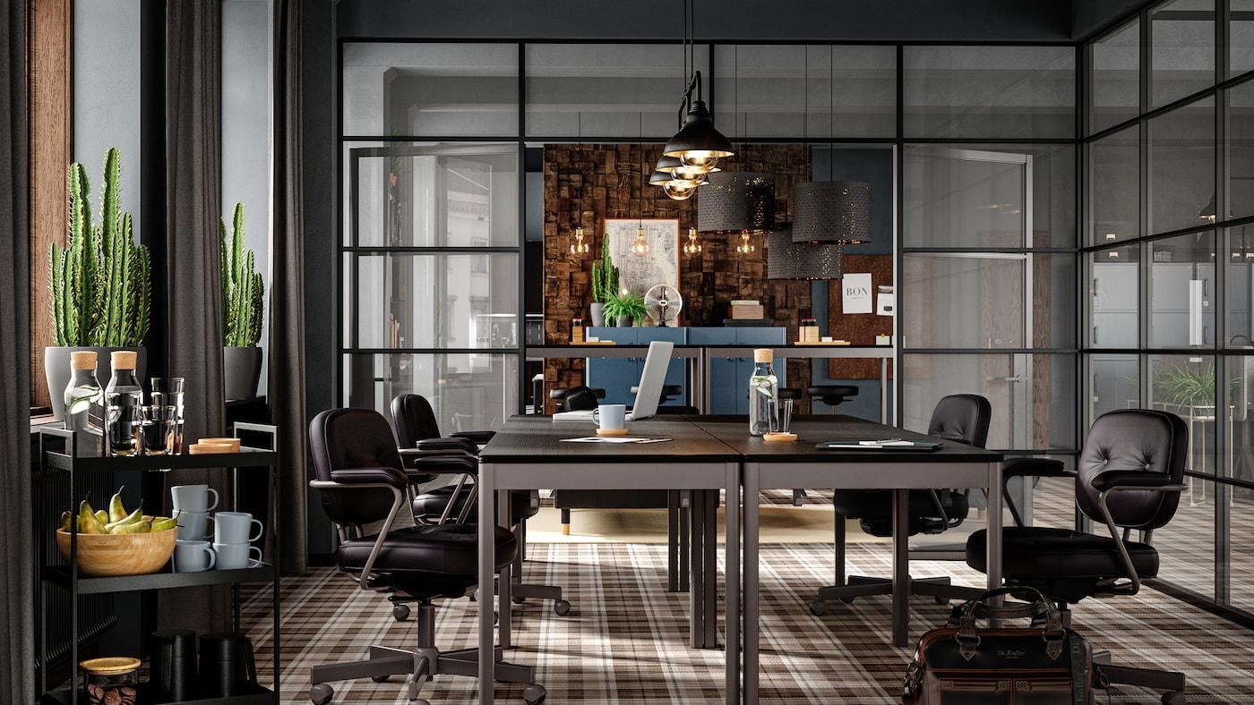 Sala de conferencias con muebles oscuros, paredes de cristal, suelo marrón a cuadros, sillones de piel y cactus en la ventana.