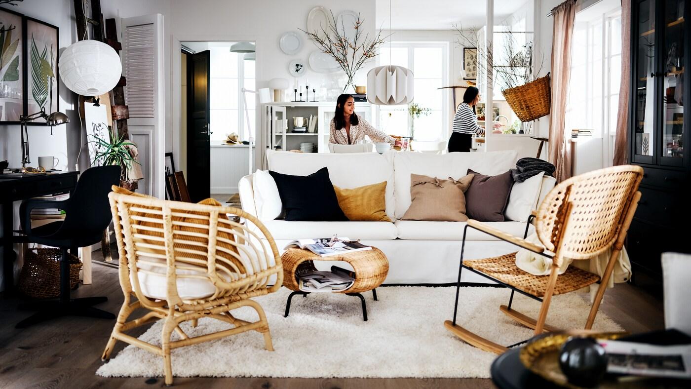Sala de estilo rústico em tons de branco com duas mulheres atrás de um sofá BACKSÄLEN em branco, à frente de um tapete e duas poltronas.