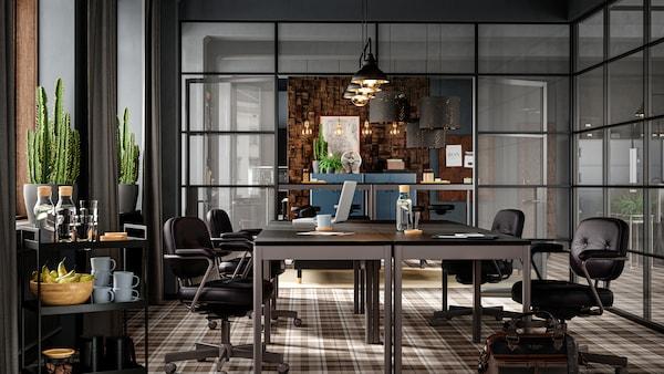 Sala riunioni con mobili scuri, pareti in vetro, pavimento con disegno scozzese marrone, sedie in pelle e cactus vicino alla finestra.