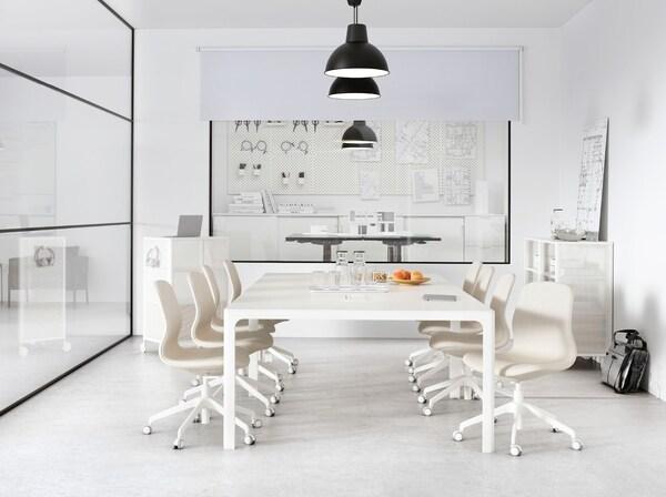 Sala riunioni con un grande tavolo bianco e parete in vetro. Al soffitto è appesa una fila di lampade a sospensione SKURUP nere – IKEA