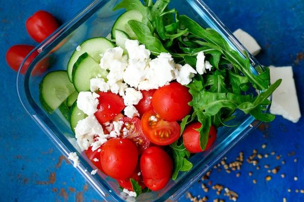 Salat mit Rucula, Feta, Tomaten und Gurken.
