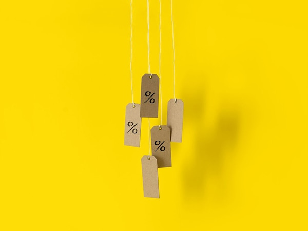 Sale price tags hanging over a yellow background