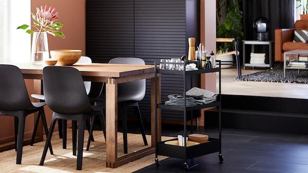 Salle à manger avec des chaises anthracite, une table en chêne plaqué teint, un rangement noir, un tapis en jute et une desserte avec de la vaisselle.