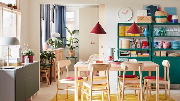 Salle à manger avec table et chaises en bouleau, tapis jaune, combinaison de rangement en blanc/gris-vert et suspensions rouge foncé.