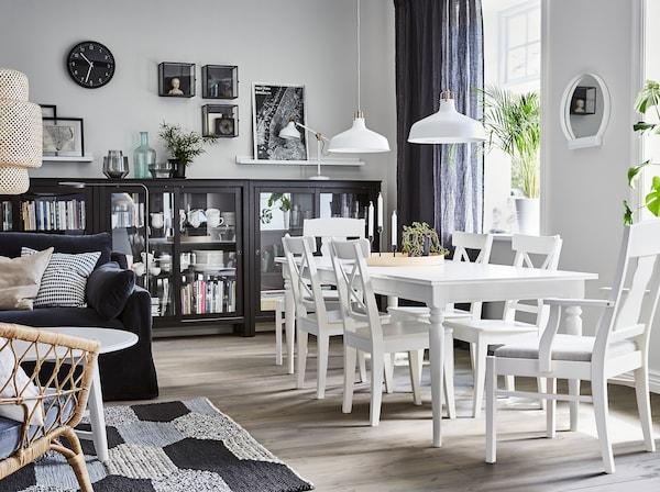 Salle à manger de style traditionnel à côté du salon avec la table extensible et les chaises INGATORP avec siège rembourré. La vaisselle est rangée dans la vitrine HEMNES en noir.