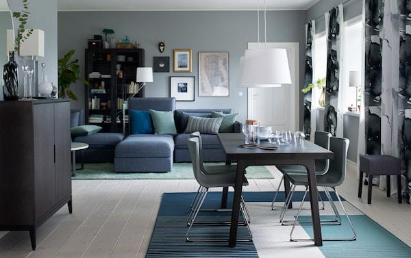 Salle à manger de taille moyenne meublée d'une table à manger brun foncé pour quatre personnes et quatre chaises en cuir vert avec pieds chromés.