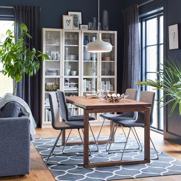 Salle à manger en brun et gris avec quatre chaises rembourrées VOLFGANG en chrome et gris moyen et la table MÖRBYLÅNGA en plaqué chêne.