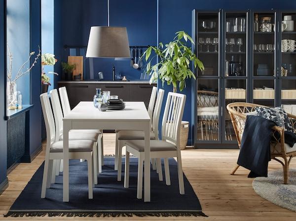 Salle à manger peinte en bleu foncé, table et chaises de couleur claire. Chaises à siège rembourré. Aperçu de la cuisine en arrière-plan.