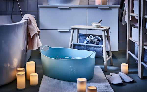 Salle de bain éclairée par des bougies bloc LED dispersées; un tabouret placé à côté d'une bassine, des fleurs flottant dans celle-ci.
