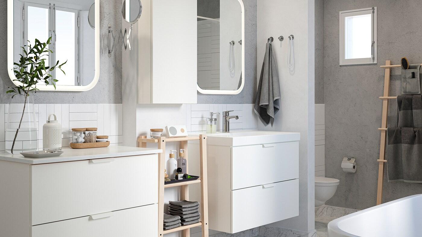 Salle de bain revêtue d'un carrelage blanc avec des murs gris, deux lavabos et une étagère en bouleau avec des serviettes et des produits de beauté.