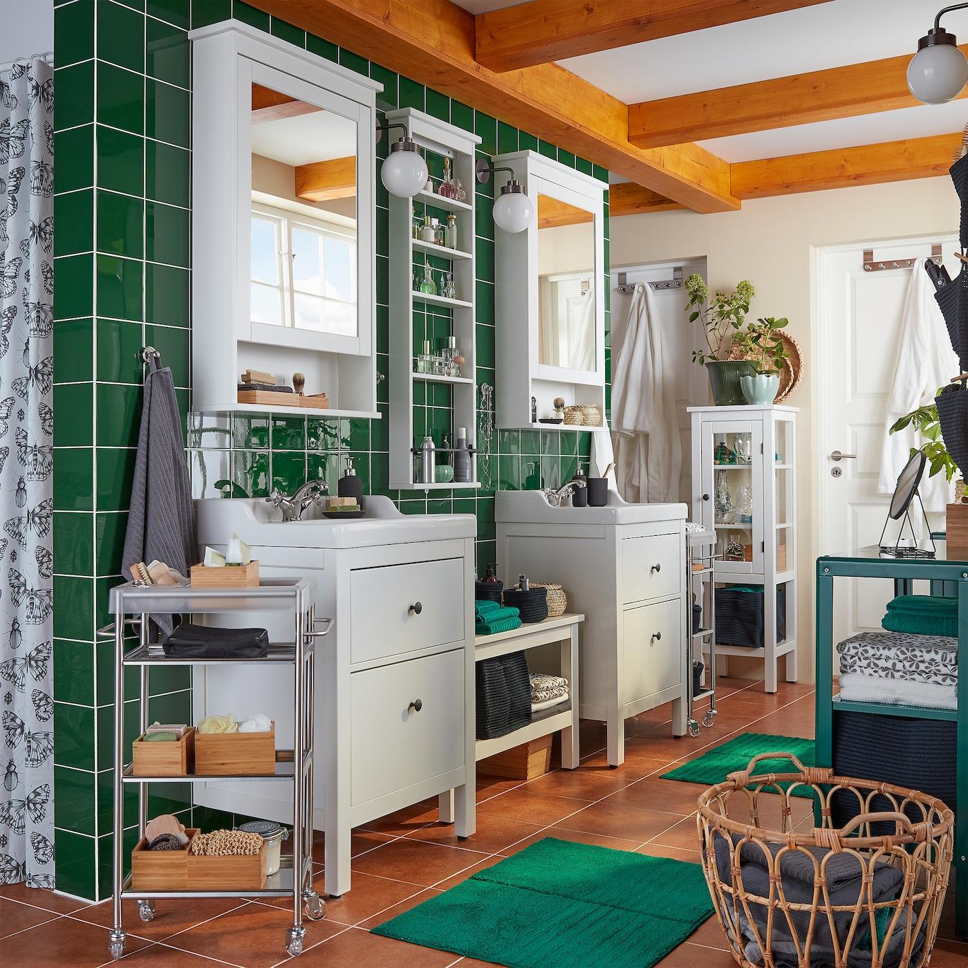 Salle de bains à carreaux verts, deux meubles-lavabos, deux armoires à miroir, un panier en rotin et deux tapis de bain verts.