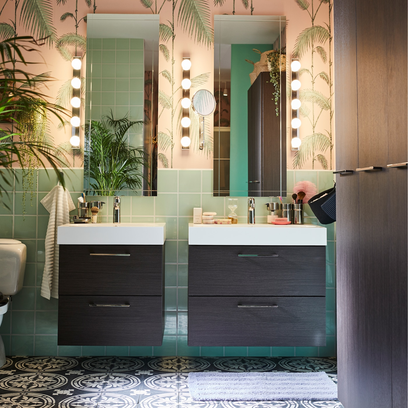 Salle de bains en vert et rose, sol à motif noir et blanc. Deux meubles-lavabos brun-noir placés l'un à côté de l'autre.