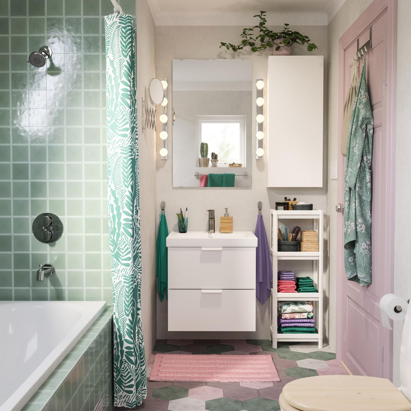 Salle de bains rose et turquoise avec lavabo et armoire murale blancs, tapis de bain rose et rideau de douche turquoise.