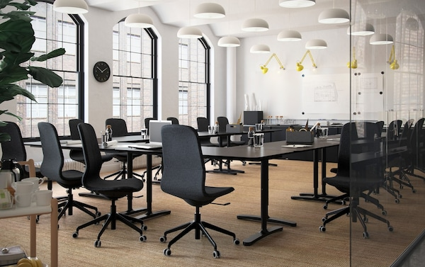 Salle de conférence moderne dotée de murs blancs et de grandes fenêtres. Bureaux BEKANT brun-noir et chaises pivotantes et ergonomiques LÅNGFJÄLL.