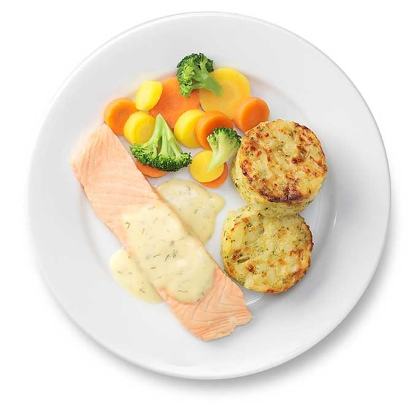 Salmon with vegetable medallions on a white plate.